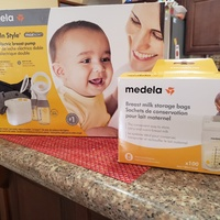 Medela double electric breast pump with breast milk storage bags.